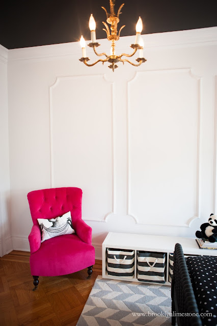White walls and hot pink chair in girl's bedroom
