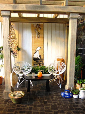 One-twelfth scale modern miniature patio scene with wire chairs, a gazebo and many plants.