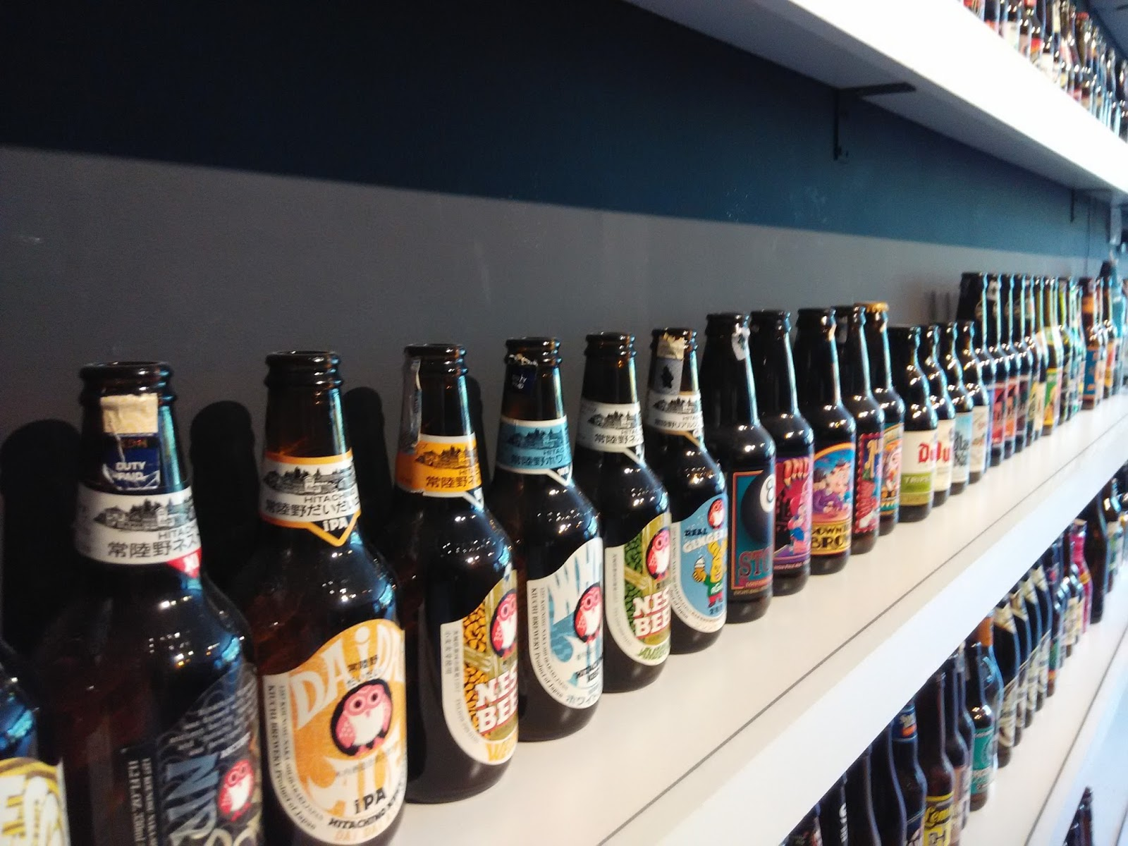 Shelf Display With A Glow Of Light Showcasing Many Handcraft Beer Bottles And Wines From All Around The World Just Like Compelling Art On