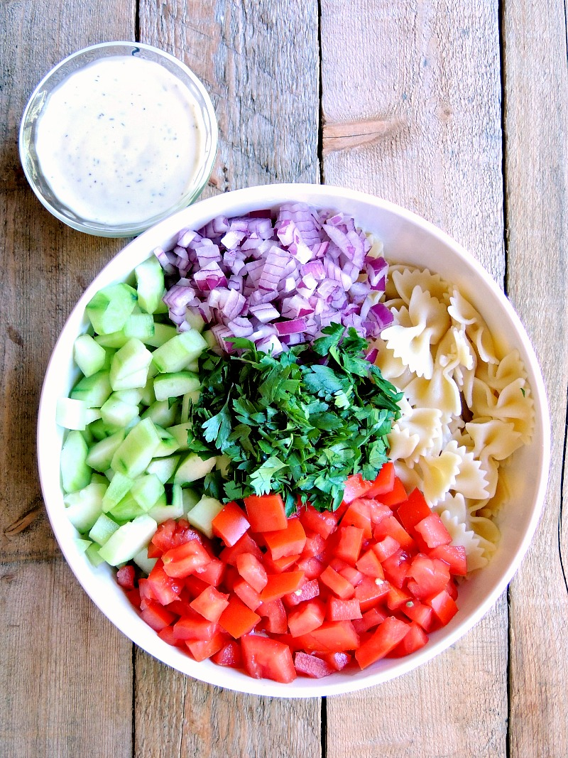 Ingredients for the Mediterranean Pasta Salad in a bowl with a with a small bowl of salad dressing next to it on a wooden background