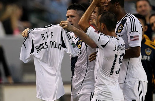 LA Galaxy player Robbie Keane holds up a jersey with 'RIP James Nolan' printed on the back