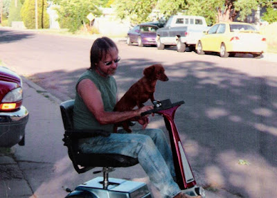 Dachshund Pup named Dixie riding with Jimmy down sidewalk on an Amigo scooter