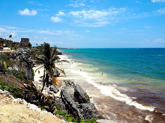 Palm trees & ruins on the cliff side, overlooking the beach and ocean at Tulum, Mexico