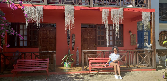 girl sitting on a bench in front of rooms twelve and thirteen at idlers rest hotel, Chevy Takes The Mic Jamaican Travel Blog Series Adventures in St. Elizabeth Jamaica, things to do in Jamaica