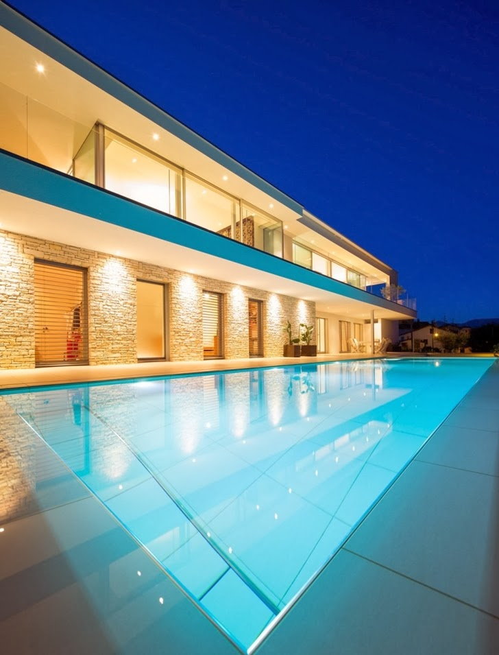 Facade and swimming pool in Beautiful House Lombardo by Philipp Architekten at dusk
