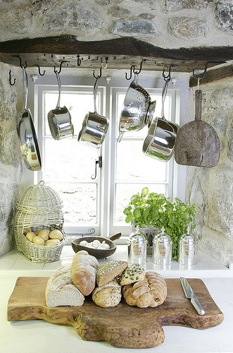 This french countryside kitchen is accented with hanging pots and a rustic cutting board with fresh french bread