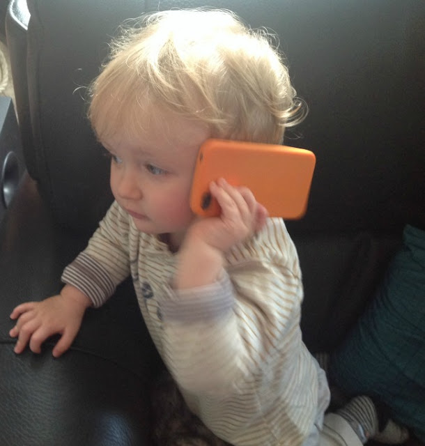 toddler with mobile phone to his ear