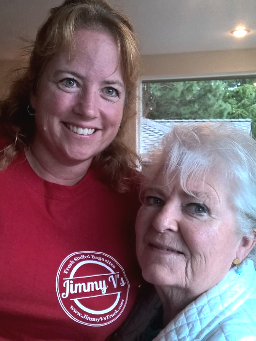 Shanna wearing her JImmy Vs Branded TShirt hugs her Other Mom at a Gathering