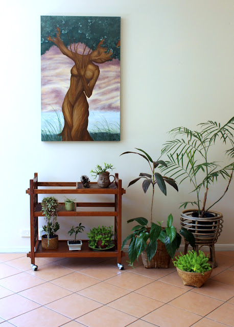 indoor plant decor with wall painting and vintage bar cart