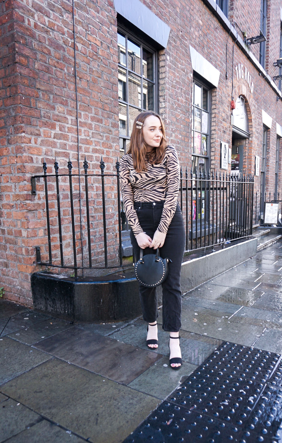 Christmas night out look: zebra print lurex top, black jeans, black and gold accessories