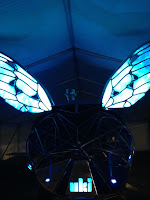 Steampunk bug with glowing wings and a DJ in a top hat on top of it