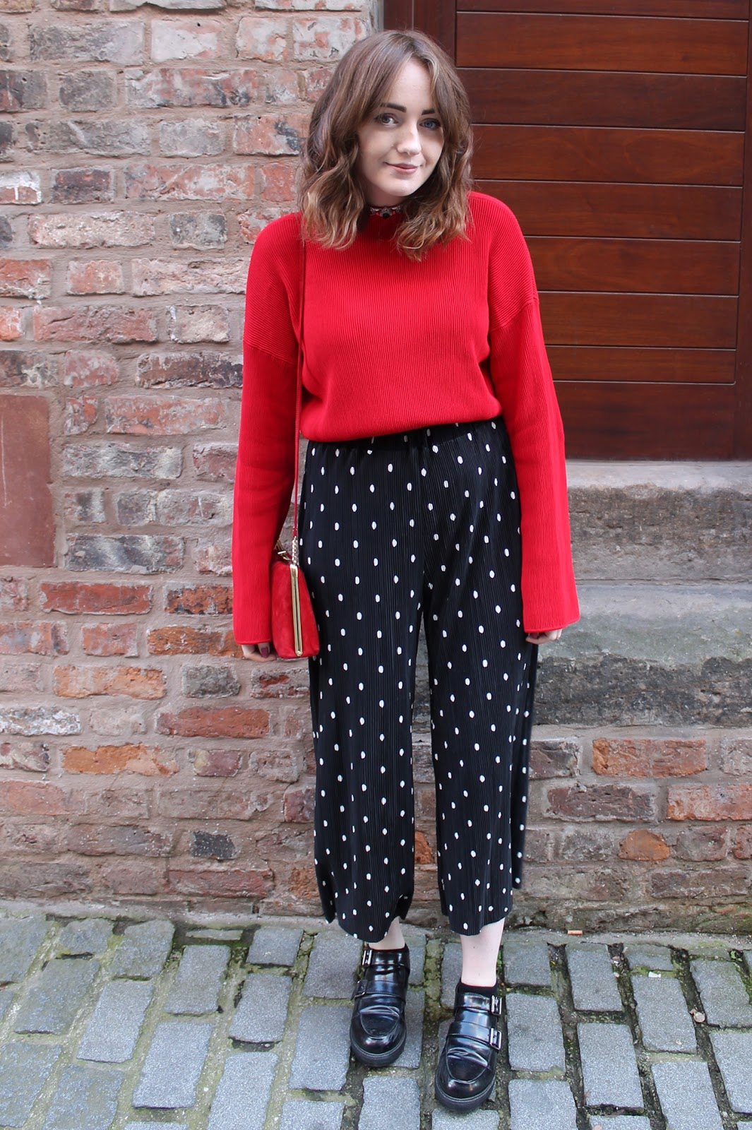 red funnel neck jumper with oversized long sleeves, polka dot trousers, monk shoes