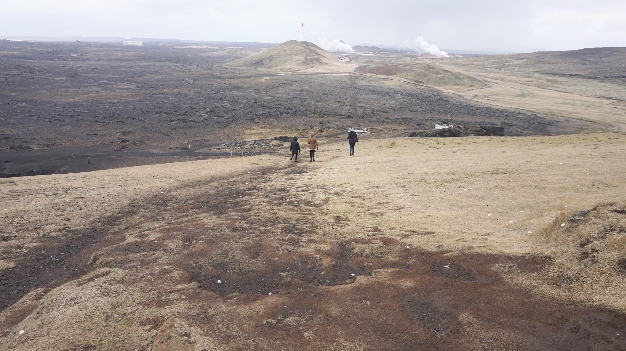 three women walking down huge hill in the middle of rural Iceland
