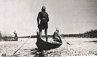 Madan poling and paddling a canoe