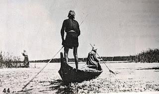 Madan poling and paddling a canoe