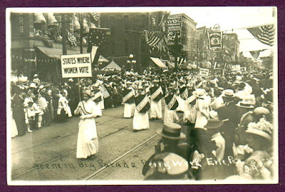"Woman in white dress carrying sign ""States where women vote"" in parade, Erie PA 1913"