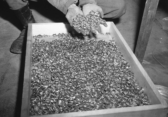 A U.S. soldier inspects thousands of gold wedding bands taken from Jews by the Germans and stashed in the Heilbronn Salt Mines, on May 3, 1945 in Germany.