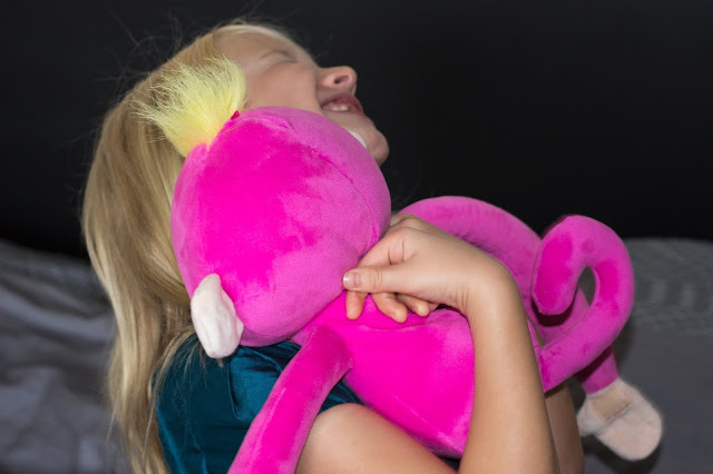A girl hugging a pink long limbed cuddly monkey