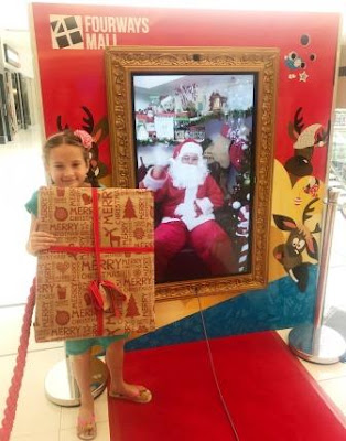 Girl next to Santa Live from the North Pole
