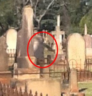 This photo from 2012 is claimed to be of a 'ghost hovering near a grave'. What it looks more like is shadows on a headstone creating a pareidolia effect.
