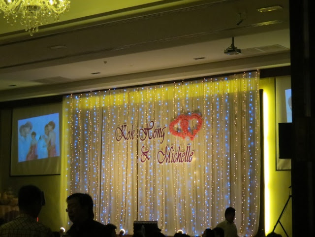 stage decorated with fairy lights, names of couple