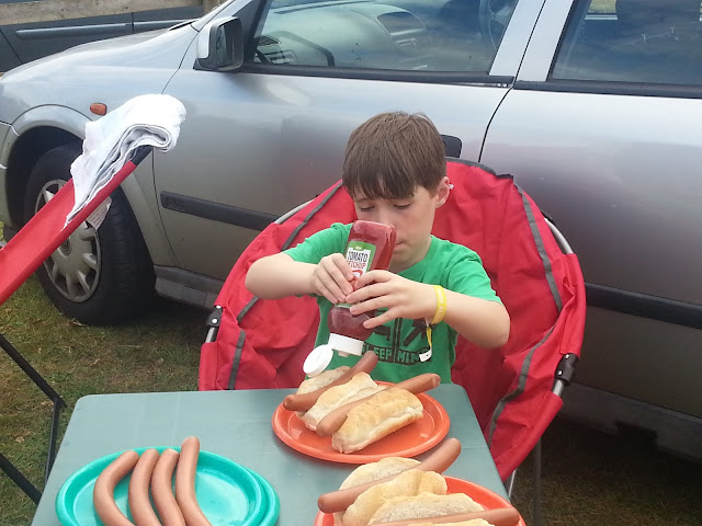 Boy sitting at camping table with hotdogs and ketchup.