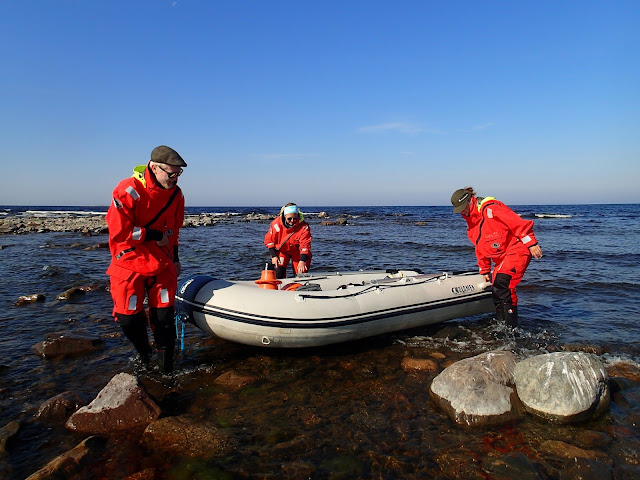 Kolme henkeä nostamassa kumivenettä rantakivikossa
