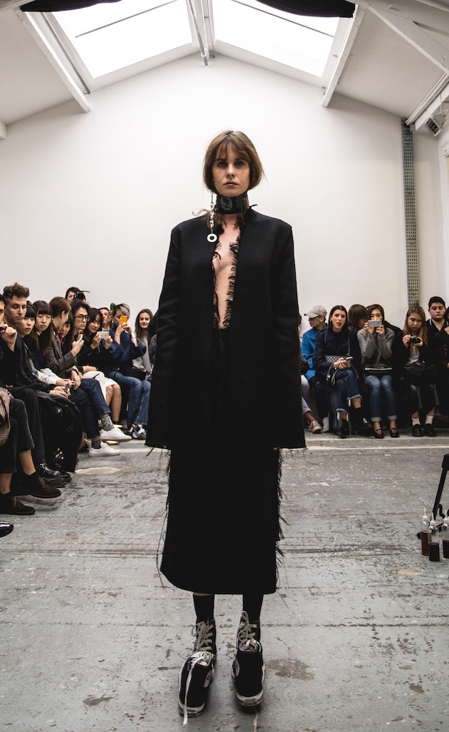 Model in all black with raw edge hems and sneakers attached to sneakers walking down runway