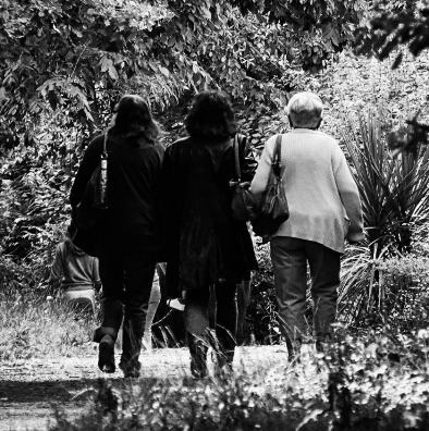 A black and white photo of three women walking, arms linked, taken from behind