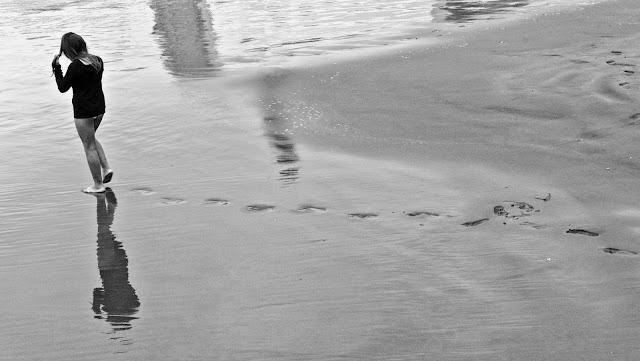 Joven caminando en la playa.B/W