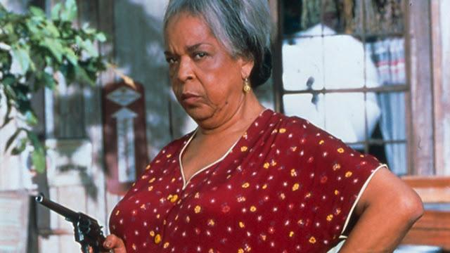 Mulher na porta de uma cabana segurando uma arma (Filme Milagre na Cabana Dublado e Completo)