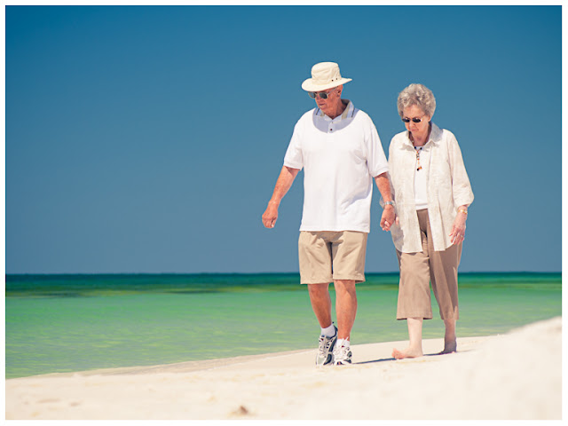 grandparents walking on the beach