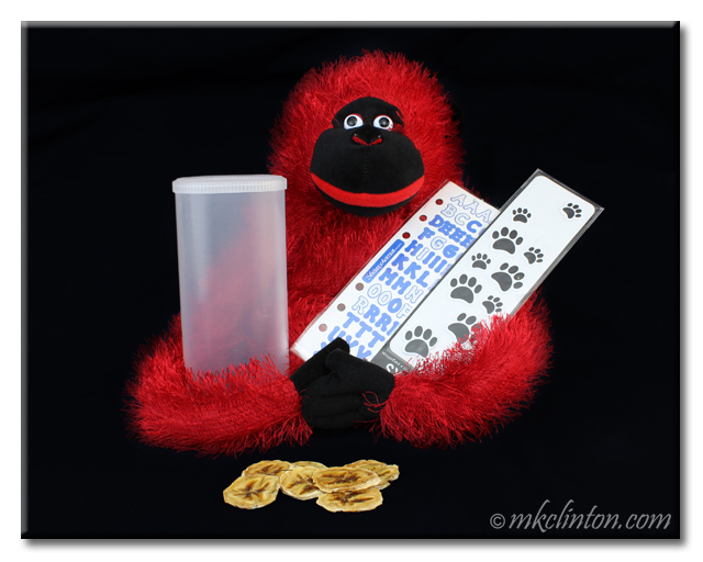 Stuffed red toy monkey holding craft stickers and empty clear canister.
