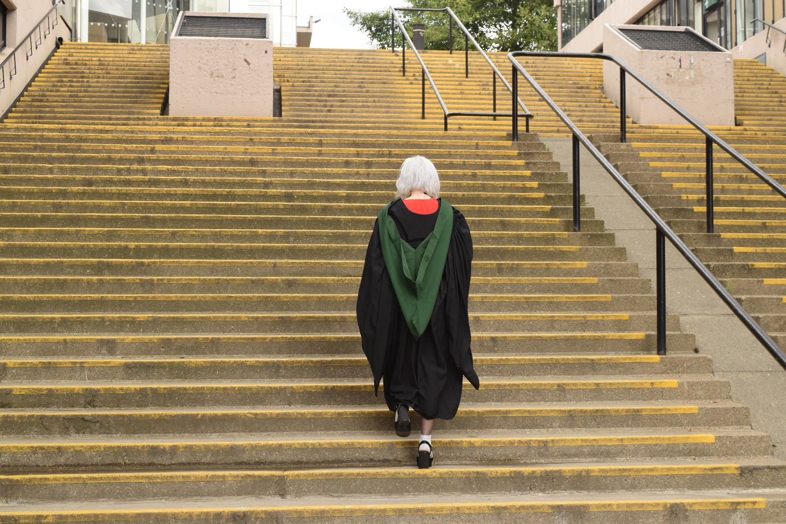 Leeds graduate in gown on steps near Roger Stevens building