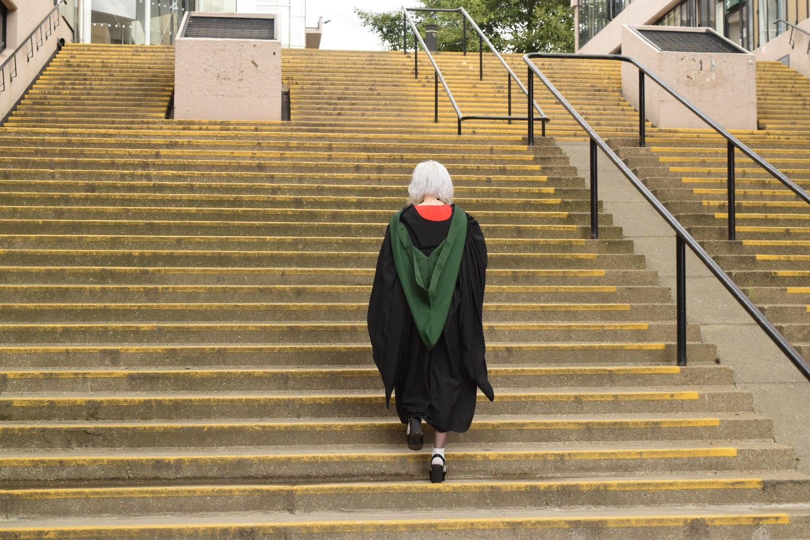 Leeds graduate in gown on steps near Roger Stevens building