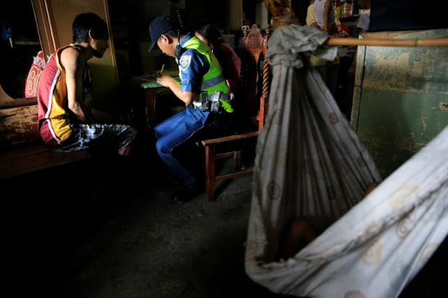 "Image Attribute: A member of the Philippine National Police (PNP) documents a self-confessed drug user who voluntarily surrendered to the police on their ""Operation Tokhang (approach and talk)"" in Pasig city, metro Manila, Philippines  September 15, 2016. Picture taken September 15, 2016.    REUTERS/Romeo Ranoco"