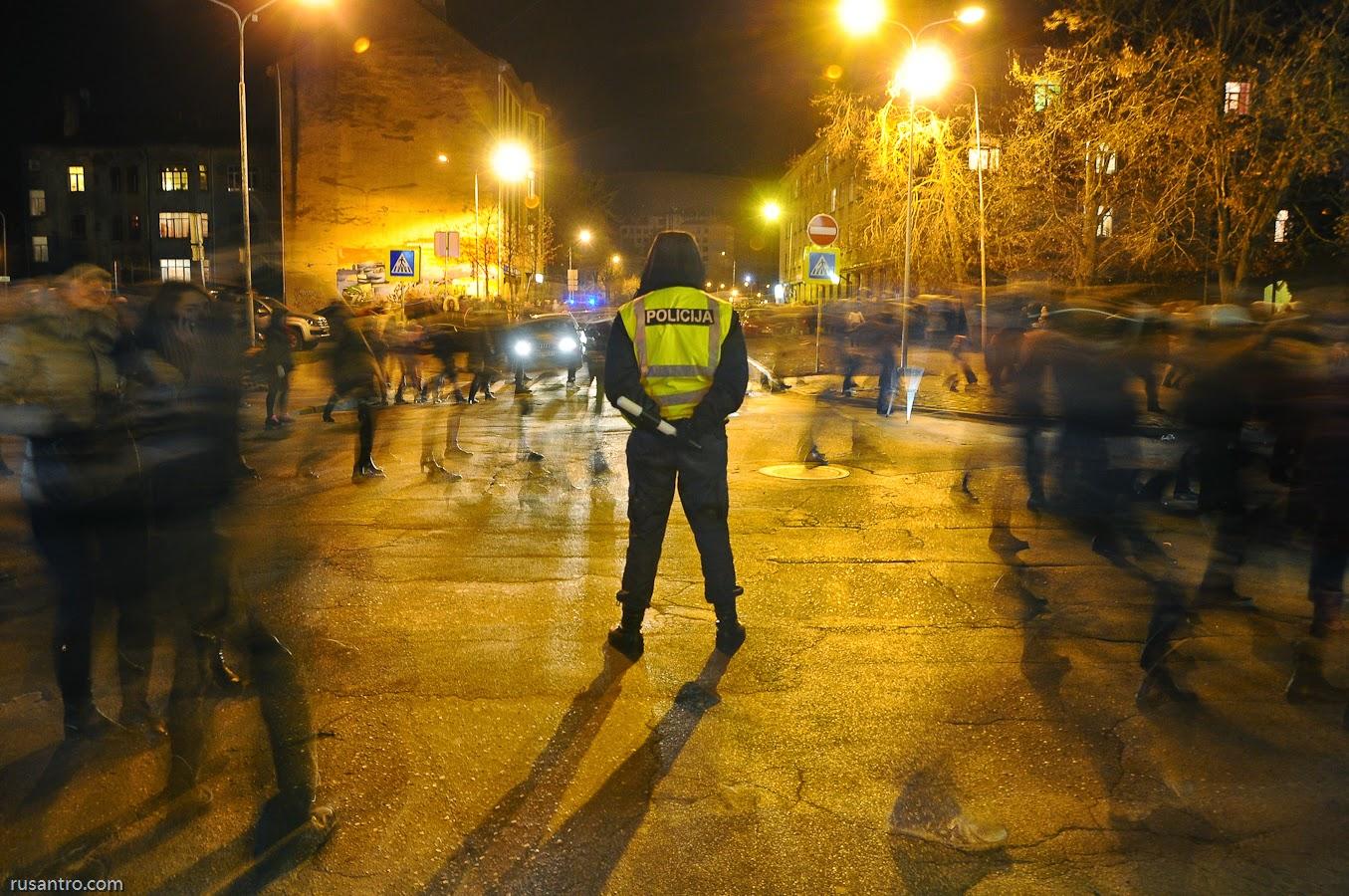 Policists atstarojošā vēstā stāv ejošo gājēju pūļa vidū