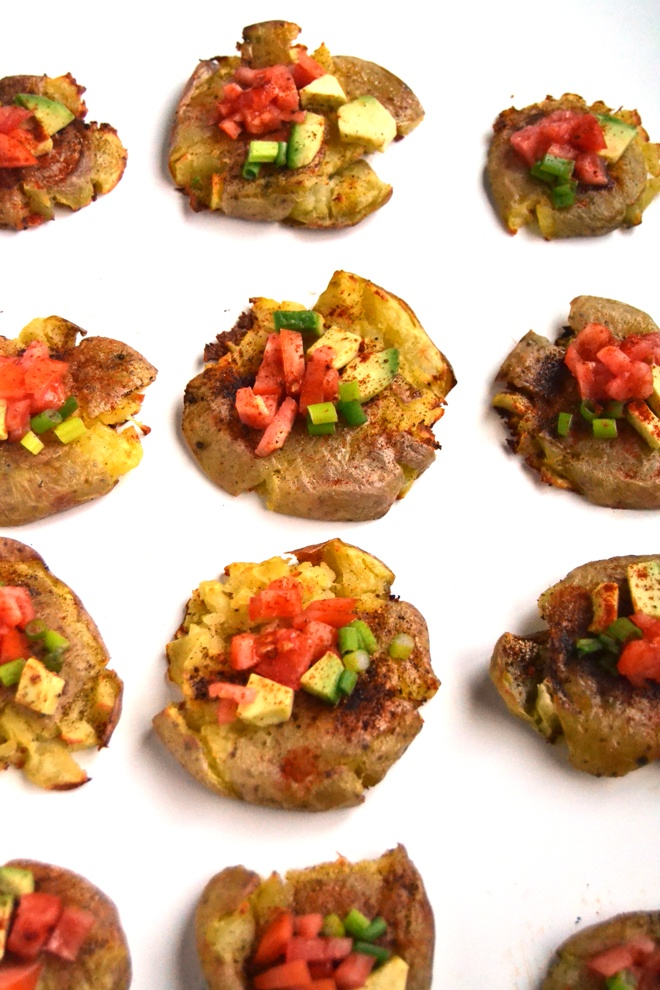 Spicy Smashed Potatoes are crisp on the outside, soft on the inside and loaded with spicy flavors and topped with avocado, tomato and green onion for the perfect side dish or appetizer. www.nutritionistreviews.com