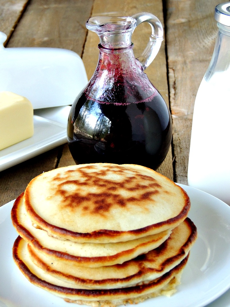 Glass bottle with Homemade Blueberry Syrup in it on a wooden table. Butter dish, glass of milk, and pancakes on a white plate with it.