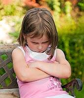 Küsmüş ve kollarını önde bağlayarak somurtan bir kız çocuğu