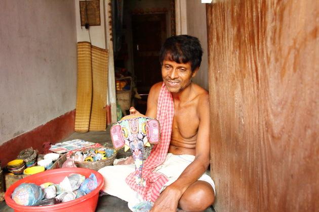 Elderly Raghurajpu Chitrakaar showing me his papier mache creations