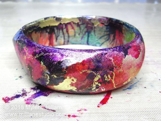 Red, blue and purple alcohol inks blended together with gold marbling on a resin bangle base.