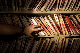 Man's hand reaching for medical records on shelf
