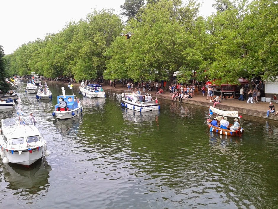 A shot of different sized boats going down the River Great Ouse