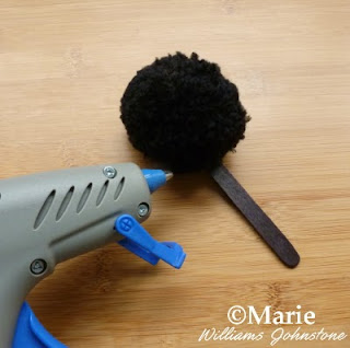 Hot glue gun used to stick a black yarn pom pom onto a popsicle stick