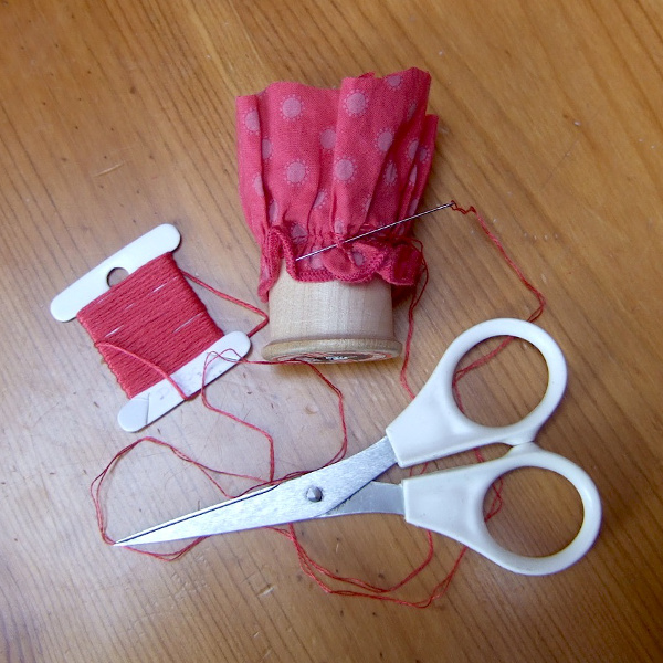 Covering the top of a thread spool with red fabric