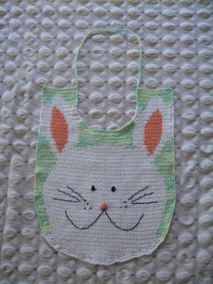 A crocheted baby bib with the shapes of a white rabbit head and ears worked in intarsia.  The face is embroidered in black thread except for the nose which is satin stitched in an apricot pink.