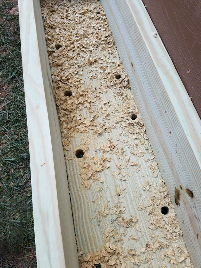 drilling holes on the bottom of wooden flower box for drainage purposes