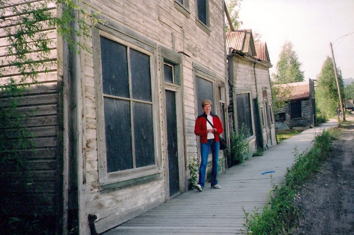 woman next to old wooden house and sidewalk in Yukon