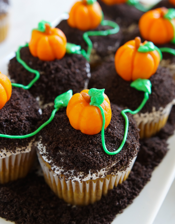 spiced pumpkin cupcakes, topped with buttercream, crushed cookies, and the cutest marzipan pumpkins